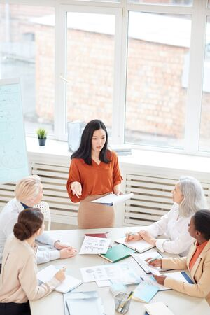 Vertical portrait of successful Asian businesswoman presenting project plan to group of female colleagues while standing by table during meeting in conference room Banque d'images