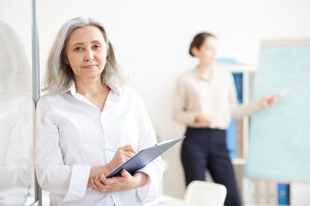 Waist up portrait of long-haired senior businesswoman looking at camera and holding clipboard while leaning against glass wall in office, copy space right Foto de archivo