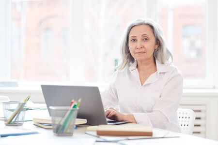 Portrait of successful senior businesswoman looking at camera while using laptop sitting in white office against window, copy space Standard-Bild