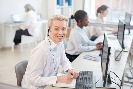 Portrait of female operator wearing headset and smiling at camera while sitting in row in call center or office interior, copy space