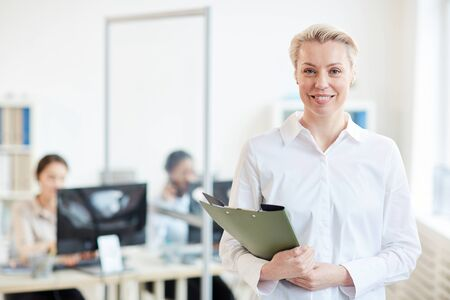Waist up portrait of successful female manager smiling at camera with group of office workers in background, copy space