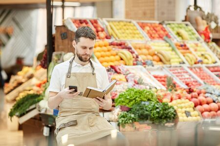 Portrait of bearded man calling supplier while selling fresh fruits and vegetables at farmers market, copy space