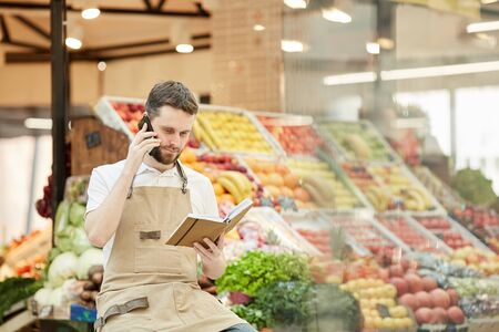 Portrait of bearded man speaking by smartphone while selling fresh fruits and vegetables at farmers market, copy space Stockfoto
