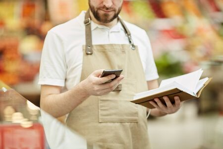 Cropped portrait of bearded man calling by smartphone while doing inventory count in supermarket, copy space Stockfoto