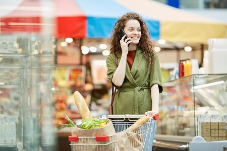 Waist up portrait of smiling young woman speaking by smartphone while enjoying grocery shopping in supermarket and pushing cart, copy space