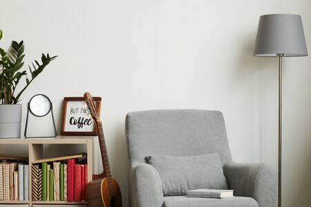 Background image of cozy modern interior with minimal decor items and grey armchair against white wall, copy space above