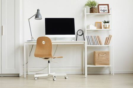 Full length view at minimal home office design with wooden chair and white computer desk against white wall, copy space