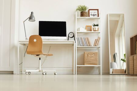Low angle view at all-white modern interior with focus on empty home office workplace, copy space