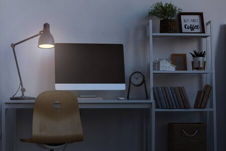 Background image of home office workplace at night, with focus on computer desk lit by dim lamp light, copy space