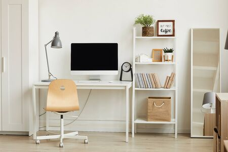 Clean background image of minimalistic apartment interior with focus on computer desk against white wall, copy space Stock Photo