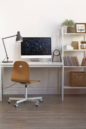 Vertical background image of contemporary home office workplace with wooden chair and PC lit by warm lamp light, copy space