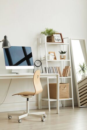 Vertical background image of empty home office workplace with wooden chair and modern computer on white desk, copy space