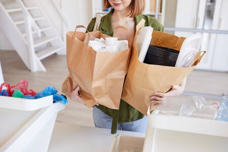 Mid section portrait of modern young woman holding paper bags with plastic items while sorting waste at home, copy space Reklamní fotografie