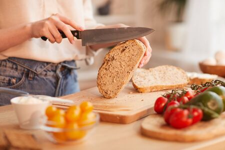 Warm-toned close up of unrecognizable woman cutting fresh wholewheat bread while making breakfast in cozy kitchen, copy space