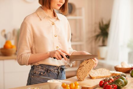 Mid-section portrait of modern young woman cutting fresh wholewheat bread while making breakfast in cozy kitchen, copy space
