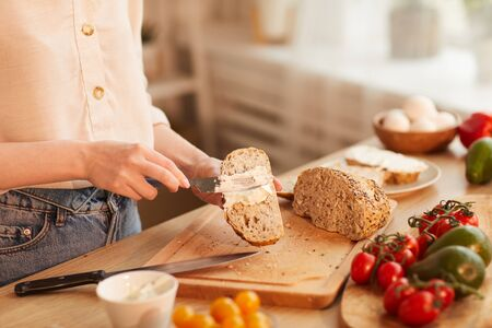 Warm-toned close up of unrecognizable woman making sandwiches while preparing breakfast in cozy kitchen, copy space