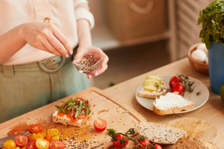 Warm-toned close up of unrecognizable woman preparing healthy breakfast sandwiches with cherry tomatoes and herbs over wholewheat bread, copy space