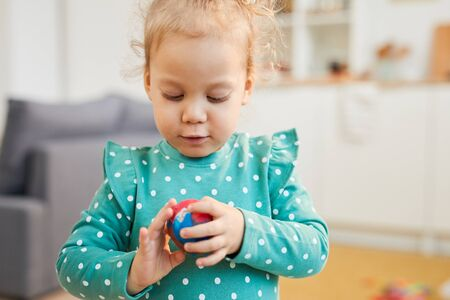 Little Caucasian girl wearing turquoise polka dot clothes making colourful modelling clay ball, horizontal portrait shot Stock fotó