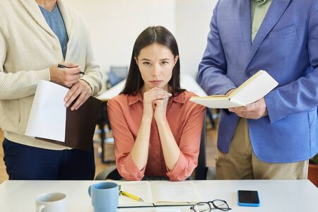 Angry young Caucasian woman sitting at office desk feeling stressed out at work, unrecognizable colleague and boss annoying her