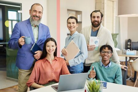 Horizontal group portrait of happy stylish business people working in modern company, looking at camera smiling