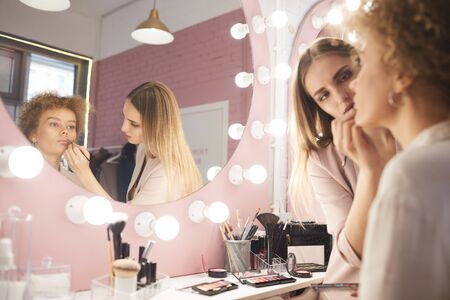 Reflection portrait of young woman applying make up on client by vanity mirror in pink dressing room interior, copy space