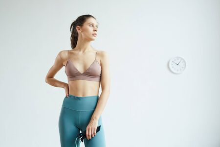 Minimal waist up portrait of fit young woman holding skipping rope and looking away while enjoying fitness workout standing against white wall with analog clock, copy space