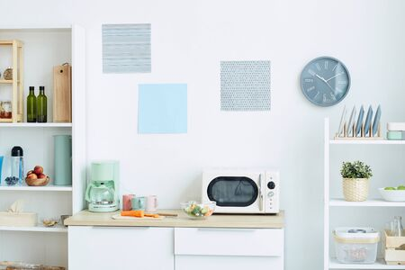 Background image of contemporary kitchen interior in pastel colors with focus on microwave oven and analog clock, copy space