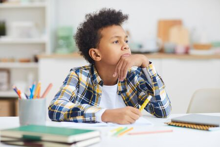 Portrait of teenage African-American boy daydreaming at desk while doing homework, copy space Stock fotó