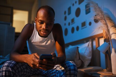 Low angle portrait of adult African-American man using smartphone while sitting on bed at night, copy space