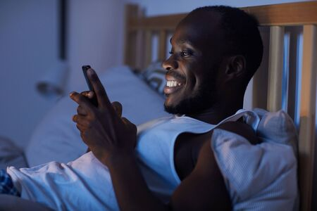 Side view portrait of smiling African-American man using smartphone in bed at night, copy space Stock fotó