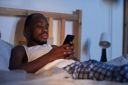 Portrait of adult African-American man using smartphone in bed at night while waiting for text message, copy space