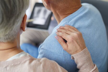 Close up of senior woman supporting husband during visit to medical clinic, focus on female hand on shoulder, copy space