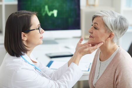 Side view portrait of female doctor examining senior woman during consultation in medical clinic Stock Photo