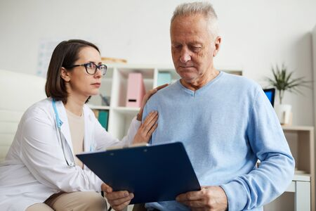 Portrait of caring female doctor comforting senior patient reading diagnosis on clipboard during consultation in clinic, copy space