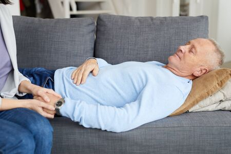 Side view portrait of senior man lying on couch with unrecognizable daughter holding his hand and supporting father, copy space