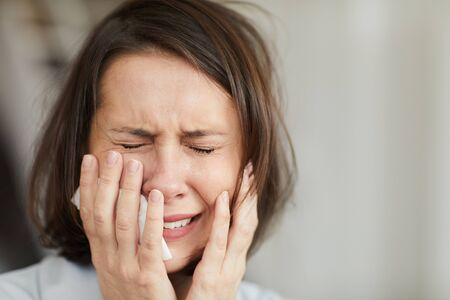 Close up portrait of disheveled adult woman crying hysterically with eyes closed and holding tissue, copy space Imagens