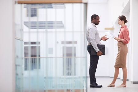Full length side view portrait of successful African-American businessman talking to young woman while standing at balcony in office building interior, copy space