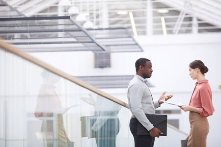 Side view portrait of successful African-American businessman talking to young woman while standing at balcony in office building interior, copy space