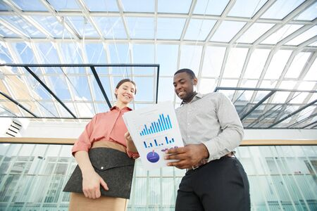 Low angle portrait of smiling African-American businessman holding documents while talking to female colleague standing under glass roof in office building, copy space Zdjęcie Seryjne