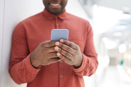 Mid section portrait of unrecognizable African-American man using smartphone while standing against while wall and smiling, focus on male hands holding phone, copy space