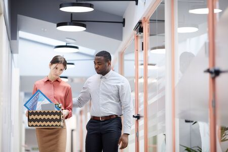 Waist up portrait of African-American man supporting young businesswoman being fired from work in office, copy space