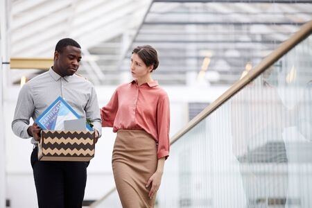 Waist up portrait of young female manager supporting African-American man leaving job, copy space Imagens