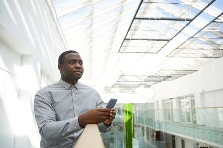 Aspiration waist up portrait of successful African-American businessman holding smartphone while standing on balcony in office building under glass roof, copy space