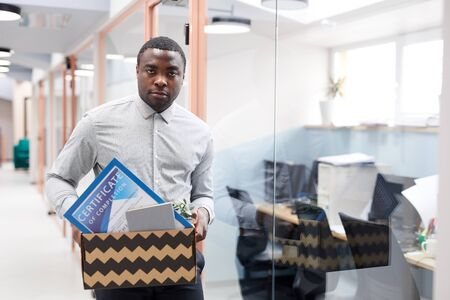Waist up portrait of young African-American man holding box of personal belongings after quitting job in office, copy space
