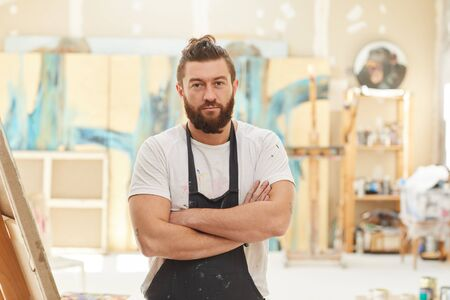 Waist up portrait of mature bearded artist standing with arms crossed and looking at camera while posing in spacious art studio lit by sunlight, copy space Stockfoto