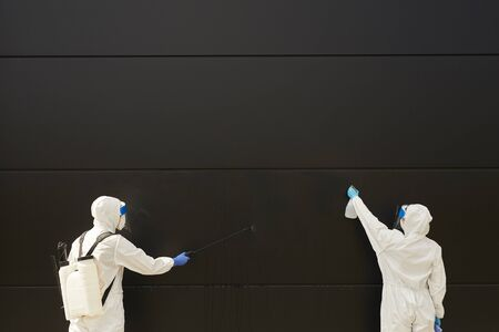 Wide angle view at two workers wearing protective gear and spraying chemicals over black building facade during disinfection or cleaning, copy space