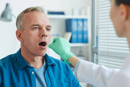 Unrecognizable female doctor taking swab sample from mouth and throat of mature man for virus test in clinic, copy space Stock Photo