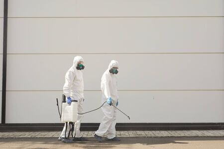 Full length wide angle view at two workers wearing protective gear and spraying chemicals outdoors during disinfection or cleaning, copy space