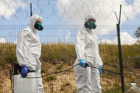 Portrait of two workers wearing protective gear and spraying chemicals outdoors standing by barbed wire fence during disinfection or cleaning in military grounds Reklamní fotografie