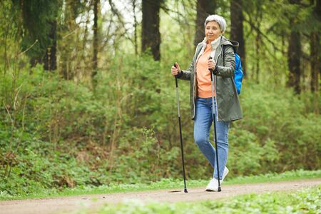Full length portrait of active senior woman enjoying Nordic walking with poles during hike in forest, copy space Zdjęcie Seryjne